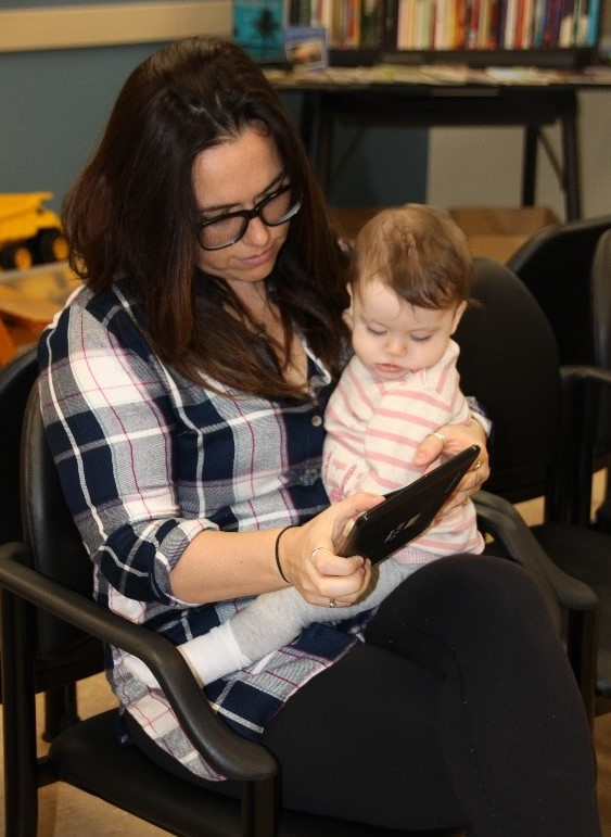 A mother holds her baby on her lap in a waiting room. Mother and baby are looking at a tablet, which the mother is holding.